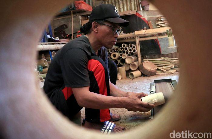 Yono (45) nampak sibuk meyelesaikan pembuatan gelas dari bambu di Desa Ciburial, Kecamatan Cimenyan, Kabupaten Bandung, Jawa Barat.