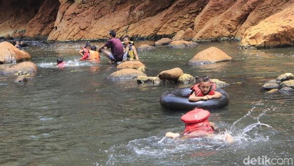 Ada juga yang berenang dengan orang tuanya sambil mengapung di atas ban karet yang disewakan pengelola (Yudha/detikcom)