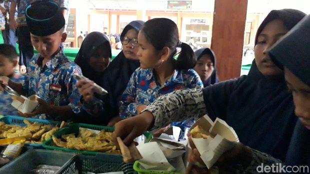 Siswa SMPN 1 Brebes makan menggunakan takir dari kertas.