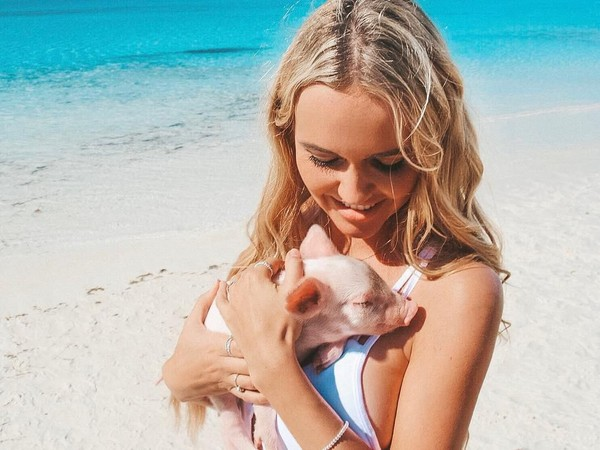 Pilot cantik ini juga tidak takut-takut saat main dengan babi di Pig Beach, Bahama. Seru sekali ya! (Foto: Instagram/@pilotmadeleine)