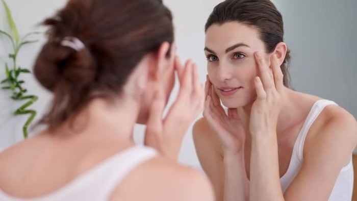 Shot of a beautiful young woman feeling her skin during her beauty routine at home