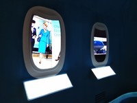 Cerita sejarah juga ditampilkan berupa video di jendela pesawat. Di bawahnya tertera keterangan tahun (Tasya/detikcom)