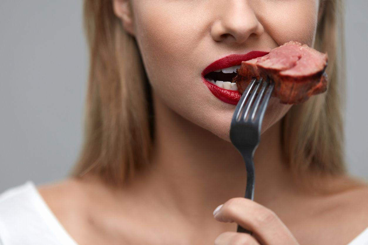 Woman Eating Meat. Closeup of Healthy Hungry Girl With Beautiful Face, Red Lips Eats Delicious Grilled Meat. Female Mouth Biting Piece Of Tasty Beef Steak On Fork. Nutrition Concept. High Resolution