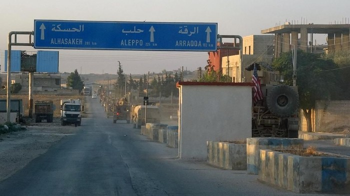 In this image provided by Hawar News Agency, ANHA,  a line of U.S. military vehicles travel down a main road in northeast Syria, Monday, Oct. 7, 2019. U.S.-backed Kurdish-led forces in Syria said American troops began withdrawing Monday from their positions along Turkeys border in northeastern Syria, ahead of an anticipated Turkish invasion that the Kurds say will overturn five years of achievements in the battle against the Islamic State group. (ANHA via AP)