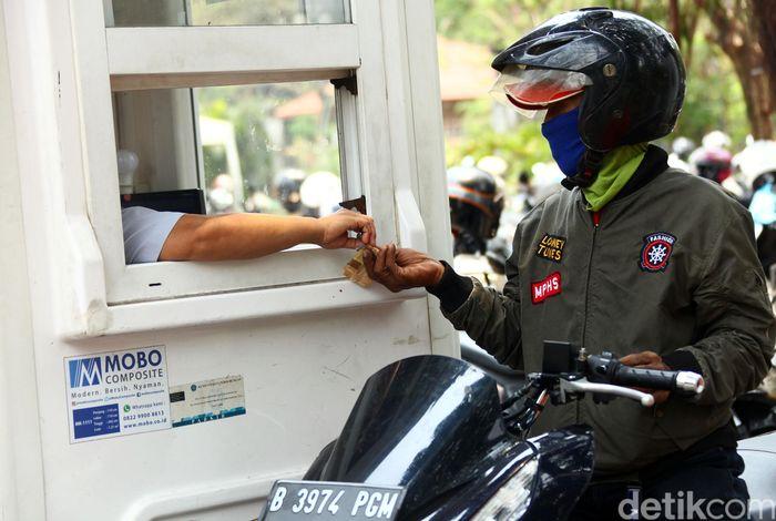 Seorang pengendara sepeda motor membayar biaya parkir di salah satu tempat parkir di Jakarta, Selasa (8/10/2019).