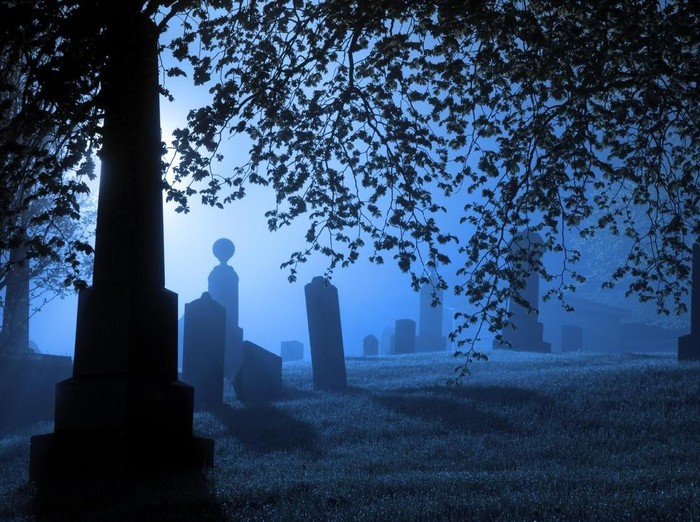 Gravestones and monuments are backlit by a bright light on a wet foggy evening.
