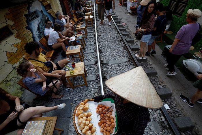 Sejumlah wisatawan nampak asyik duduk-duduk sambil menikmati makanan dan minuman di kafe yang berada persis di pinggir rel kereta api yang berada di kawasan Hanoi, Vietnam.