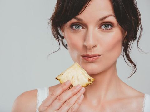 Studio shot of an attractive woman eating a snack against a gray background