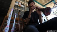 Ardi (23) sedang memainkan alat musik tradisional hasil buatan di Desa Tarajusari, Kecamatan Banjaran, Kabupaten Bandung, Jmat (11/10/2019).