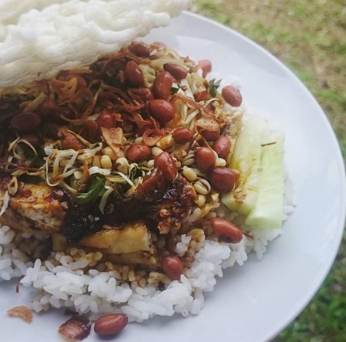 Bahan utamanya tahu goreng setengah kering. Ditaruh di atas nasi hangat ditambah tauge, seledri dan disiram saus kacang yang kental pedas. Foto : Instagram @puratragaleswara