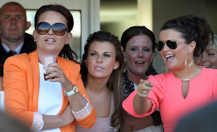 Coleen Rooney, (3rd L) wife of Manchester United and England footballer Wayne Rooney, watches the races on the second day of the Grand National meeting at Aintree Racecourse in Liverpool, north-west England on April 8, 2011. Friday is traditionally Ladies Day at the annual event which culminates in the Grand National four and a half mile steeplechase race on Saturday. AFP PHOTO/PAUL ELLIS (Photo by PAUL ELLIS / AFP)