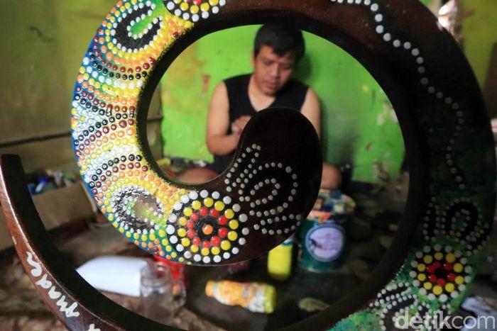 Seorang pekerja nampak sibuk menyelesaikan pembuatan souvenir bermotif batik di kawasan Rancaekek, Kabupaten Bandung, Jawa Barat.