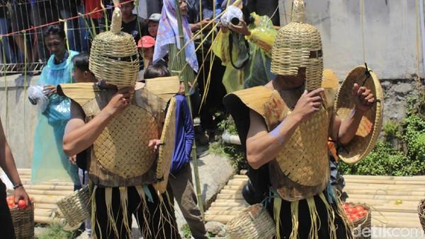 Setelah itu, para jejaka yang menjadi gladiator mengenakan perlengkapan perang, sejurus kemudian melakukan aksi lempar melempar tomat yang diikuti oleh warga. (Yudha/detikcom)