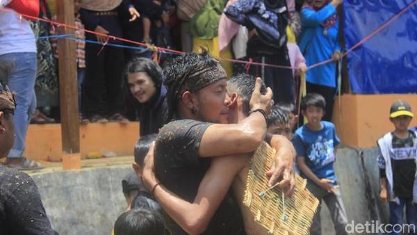 Para petarung berpelukan seusai acara dan menari dengan iringan musik di atas panggung. Lalu mereka membersihkan diri di pancuran air bergantian. (Yudha/detikcom)