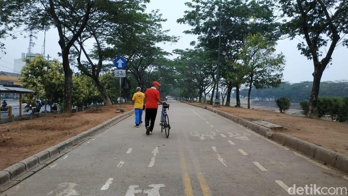 Jalur sepeda di kawasan Kanal Banjir Timur (KBT) terbentang dari Cipinang hingga Marunda. Khususnya di Cipinang hingga Duren Sawit, jalur tersebut cukup ideal karena rindang dan steril terpisah dari jalan raya.Foto: Sarah Oktaviani Alam/detikHealth