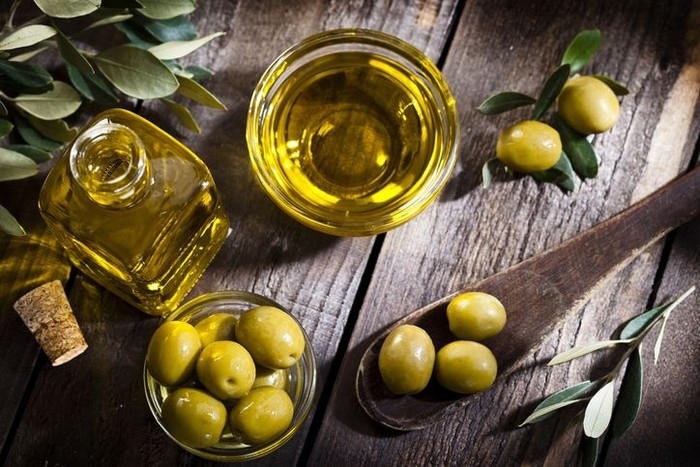 Olives assortment in bowl with oil. Top view. Copy space