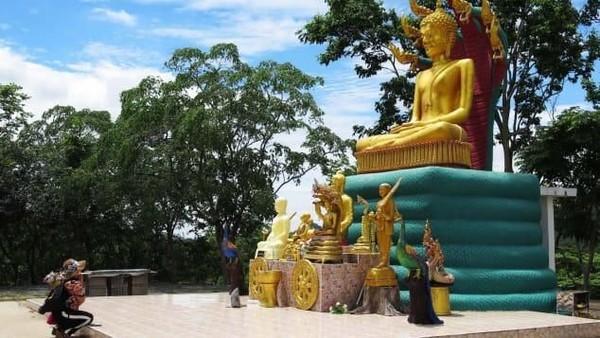 Seorang wanita Buddha berlutut di depan Patung Buddha berukuran besar di kawasan UFO ini. Sebelum mendapat kisah dari keluarga Wassana yang melihat alien, tempat ini tidak dikaitkan dengan UFO. (CNN Travel)
