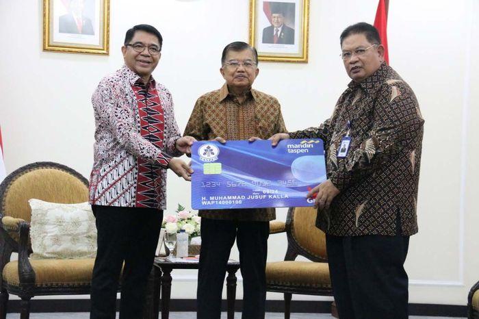 Wakil Presiden Jusuf Kalla menerima secara simbolis penyerahan manfaat Tabungan Hari Tua (THT) dari Direktur Utama Taspen Iqbal Latanro dan Direktur Utama Bank Mantap Josephus K. Triprakoso di Kantor Wakil Presiden, Jakarta, Senin (14/10).