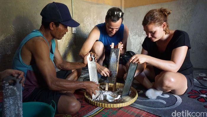 Dua orang turis mengikuti proses pembuatan minyak kelapa di Desa Kembang Kuning, Kecamatan Sikur, Kabupaten Lombok Timur. Mereka terlihat memarut kelapa.