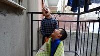 Mewakili kebahagiaan, Lensa Verde Mashad asal Suriah yang berusia 16 tahun mengambil gambar dua orang saudara laki-laki yang tengah tertawa di balkon. Istimewa/UNICEF/Mashad.