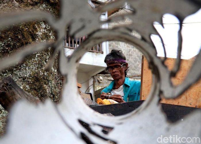 Entang Sugiri (56) tengah menyelesaikan pembuatan kerajinan ukir di Kelurahan Babakan Ciamis, Kecamatan Sumur Bandung, Kota Bandung.