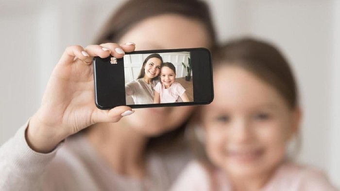 Happy mother laughing taking selfie with child daughter on smartphone at home, smiling single mom and cute girl playing making photo posing for self portrait, mommy and kid shooting instagram stories