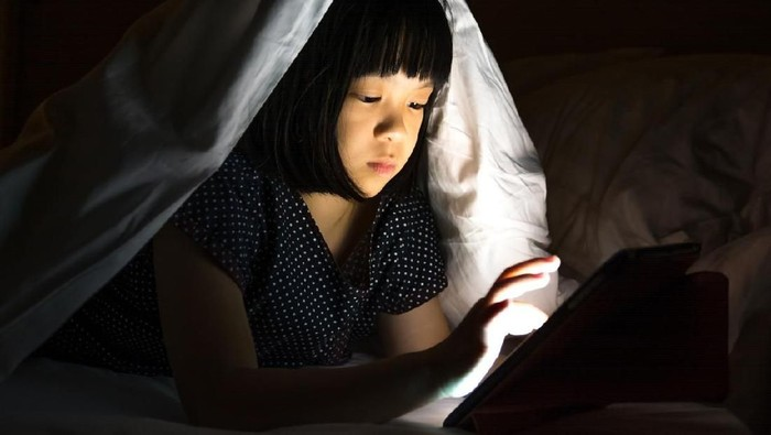 Tablet with children problem concept. Asia small female kid child girl sneaking using smartphone computer pc at night in bedroom. Adorable elementary school girl watching movie on bed.