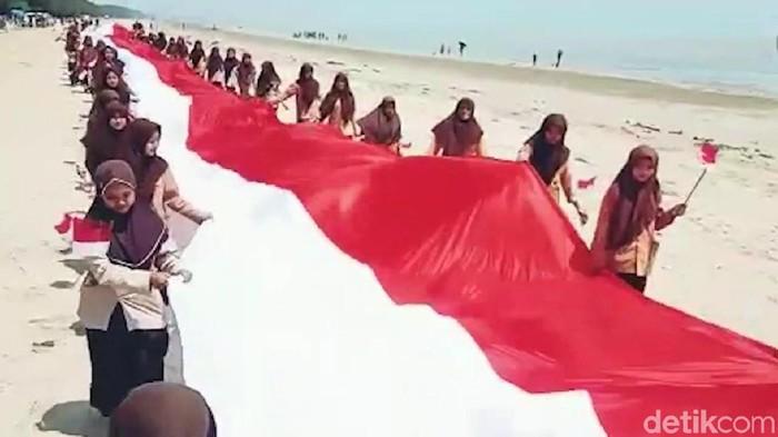 Bendera raksasa dibentangkan para pelajar (Foto: Ainur Rofiq)