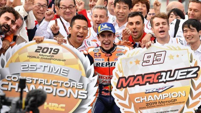 Marc Marquez bersama staf tim Repsol Honda saat mengunci gelar juara dunia MotoGP 2019. (Foto: Toshifumi KITAMURA / AFP)