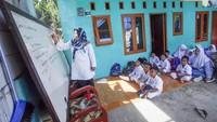 Sejumlah murid Madrasah Ibtidaiyah Mathlaul Anwar Ciangsana mengikuti kegiatan belajar mengajar di kelas darurat di depan teras rumah kontrakan warga yang berada di Tenjolaya, Kabupaten Bogor, Jawa Barat, Senin (21/10/2019).
