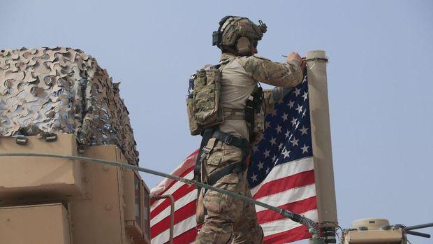 Tentara AS memasang bendera nasional AS pada kendaraan militer di kota Tel Tamr, Suriah bagian utara