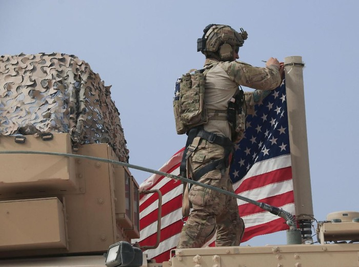 American soldier mount the U.S. flag on a vehicle near the town of Tel Tamr, north Syria, Sunday, Oct. 20, 2019. Kurdish-led fighters and Turkish-backed forces clashed sporadically Sunday in northeastern Syria amid efforts to work out a Kurdish evacuation from a besieged border town, the first pull-back under the terms of a U.S.-brokered cease-fire. (AP Photo/Baderkhan Ahmad)