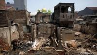 Beberapa warga bergotong-royong membersihkan barang-barang yang terbakar menggunakan sapu dan karung. Puing tersebut seperti bongkahan kayu, bantal, hingga pakaian.