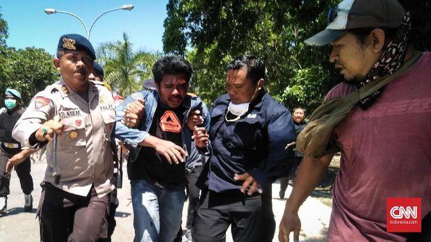 Anggota polisi (tengah) dievakuasi dari amukan pedemo.