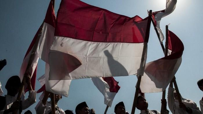 Sejumlah santri membawa bendera merah putih saat mengikuti upacara Peringatan Hari Santri Nasional Tingkat Provinsi Jawa Barat 2019 di Lapangan Gasibu, Bandung, Jawa Barat, Senin (22/10/2019). Pemerintah Jawa Barat memberikan sejumlah bantuan motor listrik dan hadiah umroh bagi santri, pondok pesantren serta DKM se-Jawa Barat pada  Peringatan Hari Santri Nasional 2019 yang bertema Santri Indonesia Untuk Perdamaian Dunia. ANTARA FOTO/Novrian Arbi/foc.