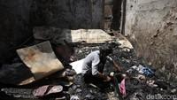 Seorang warga nampak mencari benda-benda yang masih dapat diselamatkan dari rumahnya yang telah hangus terbakar di kawasan Jatinegara, Jakarta.
