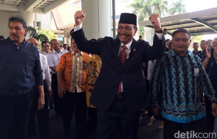 Luhut nampak mengangkat kedua tangan mengepal begitu tiba di Kementerian Koordinator Kemaritiman. Senyum semringah pun nampak di bibirnya.