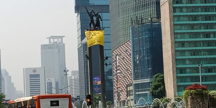 Foto: Aktivis Greenpeace Indonesia memasang spanduk di Patung Selamat Datang Bundaran HI. (Eva-detikcom)