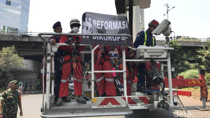 Foto: Polisi mengevakuasi dan mengamankan 5 aktivis Greenpeace Indonesia yang memasang spanduk di Patung Pancoran. (Rolan-detikcom)