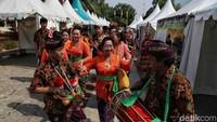 Mereka berjalan sambil bernyanyi dengan menggunakan pakaian adat dan alat musik khas dari Bali.