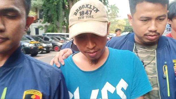 Shairil terus menunduk saat dibawa ke kantor polisi setelah diantar DKM Masjid Al-Falaah