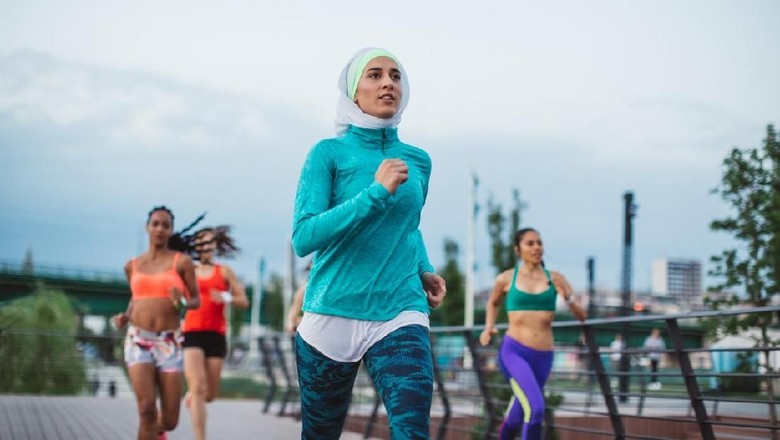 Multi ethnic group of young  women exercise outdoor, next to the river. They are wearing sport clothing, running, stretching, celebrate and support each other.