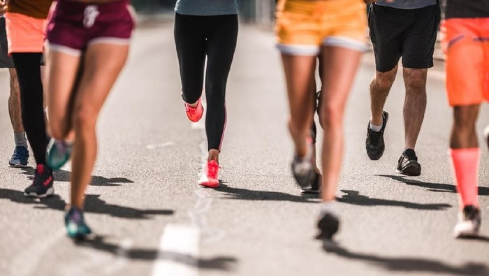 Unrecognizable athletic people running a marathon on the road.