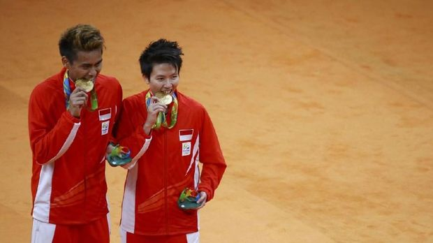 Gold medallists Tontowi Ahmad (INA) of Indonesia and Liliyana Natsir (INA) of Indonesia pose biting their medals. REUTERS/Marcelo del Pozo FOR EDITORIAL USE ONLY. NOT FOR SALE FOR MARKETING OR ADVERTISING CAMPAIGNS.