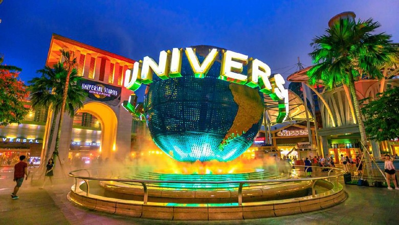 Singapore - May 2, 2018: Universal Studios world globe in green light, with tourists visiting this Hollywood movie theme park in Sentosa island.