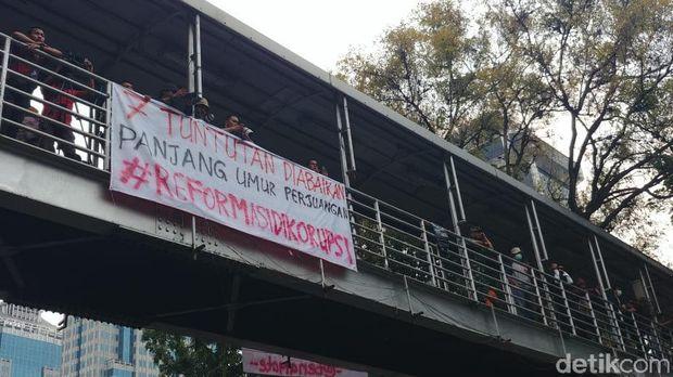 Massa di Patung Kuda mencopot spanduk Seknas Jokowi dan menuliskan #ReformasiDikorupsi di spanduk itu.