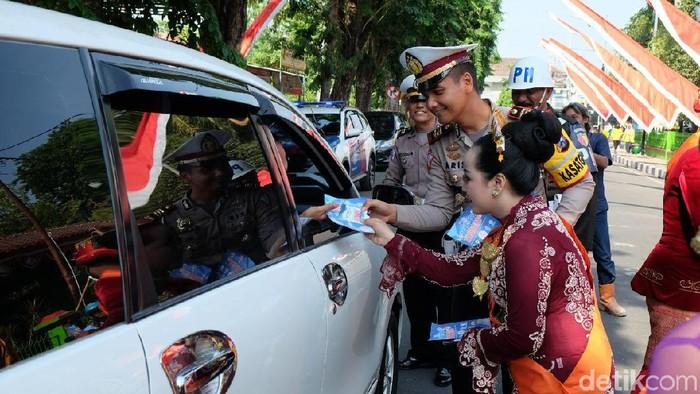 Polisi dan muda-mudi bagi pamflet keselamatan berlalu lintas (Foto: Ainur Rofiq)