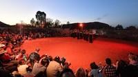 Jumat lalu (25/10) pendakian ke Gunung Uluru di Australia resmi ditutup permanen. Di hari terakhirnya, Syuku Anangu, Aborigin menghibur wisatawan yang datang dengan pertunjukan lagu dan tari-tarian. (Saeed Khan/AFP)