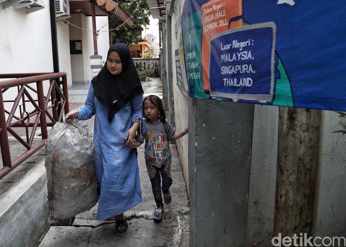 Seorang warga membawa satu karung sampah plastik yang berhasil dikumpulkannya ke Bank Sampah Majelis Taklim yang berada di Kantor Kecamatan Koja, Jakarta Utara, Selasa (29/10/2019).