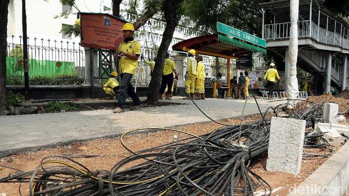 Petugas Suku Dinas Bina Marga DKI Jakarta menertibkan kabel fiber optik dan tiang penyangga yang semrawut di sepanjang Jalan Raya Salemba, Jakarta.